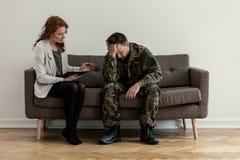 Professionele psychiater ondersteunend ongelukkige militair tijdens overleg stock foto's