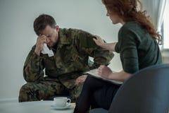 Professionele psychiater ondersteunende schreeuwende militair met oorlogssyndroom in het bureau royalty-vrije stock foto's