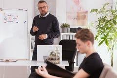 Professionele psycholoog en tiener die zijn problemen verklaren tijdens therapie royalty-vrije stock afbeelding