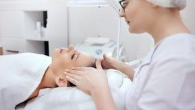 Professionele schoonheidsspecialist die medische verjonging maken en kuuroordmassage ontspannen aan jong wijfje stock footage
