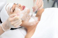 Professionele schoonheidsspecialist die vrouwelijke huid behandelen door schuim stock fotografie