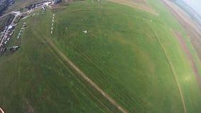 Professionele skydiver die boven groen gebied parachuteren Extreme sport Landschap stock video