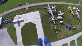 Professionele skydiver die over groene gebieden in dag parachuteren landschap landing stock videobeelden
