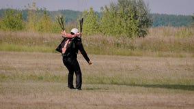 Professionele skydiver landt op een gebied in zonnige dag en zet luifel van zijn valscherm op grond stock videobeelden