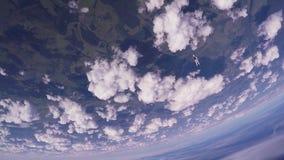Professionele skydiverssprong van vliegtuig, die in wolken parachuteren Zonnige dag stock footage