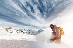 Professionele snowboarder met een rugzak die de wolk van sneeuwpoeder verlaten bij zonsondergang op een achtergrond van epische w Stock Foto's