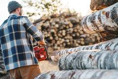 Professionele sterke houthakker die het gebruikskettingzaag van het plaidoverhemd op zaagmolen dragen royalty-vrije stock afbeeldingen
