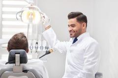 Professionele tandarts bij zijn kliniek stock foto's