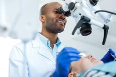 Professionele tandarts die controle van holte met microscoop leiden stock foto