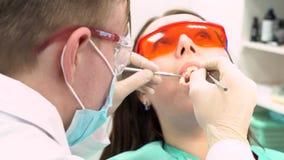 Professionele tandarts die met pati?nt in moderne kliniek, geneeskundeconcept werken media Jonge pati?nt in beschermende glazen stock videobeelden