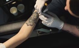 Professionele tatoegeringskunstenaar die tatoegering op hand maken stock afbeelding