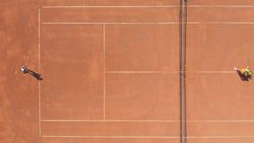 Professionele tennisbus die jonge vrouw op rood kleihof opleiden Luchttop down hommelmening stock video