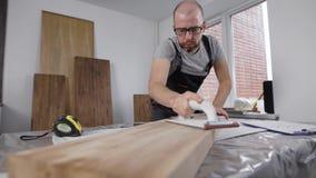 Professionele timmerman die zorgvuldig met kanten van houten raad werken stock footage