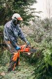 Professionele tuinman die kettingzaag met behulp van Stock Foto's