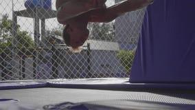 Professionele turner die op de trampoline springen en trucs in langzame motie doen stock footage