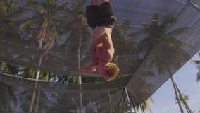 Professionele turner die op de trampoline springen en trucs in langzame motie doen stock videobeelden