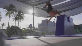 Professionele turner die op de trampoline springen en trucs in langzame motie doen stock video