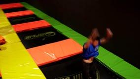 Professionele Turner die Trucs op Trampoline doen Trampolinepark stock videobeelden