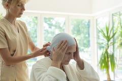 Professionele verpleegster ondersteunend ziek bejaarde met kanker in het ziekenhuis stock fotografie