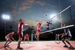Professionele volleyballspelers in actie betreffende het nachthof royalty-vrije stock afbeeldingen