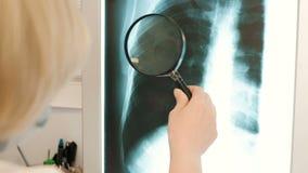 Professionele vrouwelijke arts die x-ray film van hersenen en op de telefoon 4k lezen stock footage