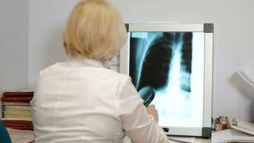 Professionele vrouwelijke arts die x-ray film van hersenen en op de telefoon 4k lezen stock video