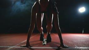 Professionele vrouwenatleet op een donkere achtergrond gotovtes om de sprint van Joggingschoenen in tennisschoenen op het spoor v stock footage