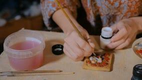 Professionele vrouwenpottenbakker die ceramische herinneringsmagneet in aardewerkworkshop schilderen stock videobeelden