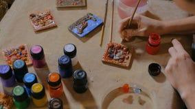 Professionele vrouwenpottenbakker die ceramische herinneringsmagneet in aardewerkworkshop schilderen stock footage