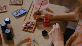 Professionele vrouwenpottenbakker die ceramische herinneringsmagneet in aardewerkworkshop schilderen stock video