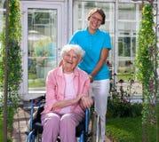 Professionele werker uit de hulpverlening achter gelukkig bejaarde royalty-vrije stock foto