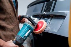 Professionele werktuigkundige die de metaaloppervlakte van de carrosserie schoonmaakt stock afbeeldingen