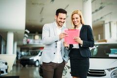 Professionele winkelbediende tijdens het werk met klant bij het autohandel drijven stock afbeeldingen