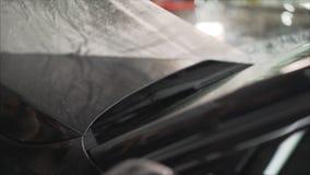 Professionell som applicerar den skyddande filmen till den röda bilen Förlagen limmar en skyddande film på huven av bilen royaltyfri fotografi