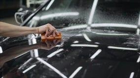Professionell som applicerar den skyddande filmen till den röda bilen Förlagen limmar en skyddande film på huven av bilen arkivfoton