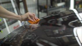 Professionell som applicerar den skyddande filmen till den röda bilen Förlagen limmar en skyddande film på huven av bilen arkivfoto