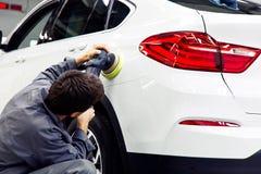 Professionelle Autopflege - Hände mit Augenhöhlenpoliermittel in der Auto-Werkstatt lizenzfreie stockfotografie