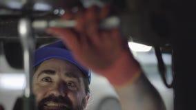 Professionelle bärtige schraubende Details des Automechanikers des Autos mit Spezialwerkzeug auf angehobenem Automobil am Reparat stock footage