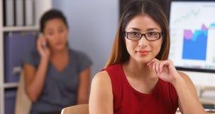 Professionelle japanische Geschäftsfrau, die durch Schreibtisch sitzt lizenzfreie stockfotografie