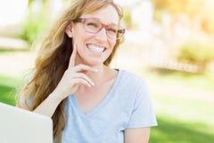Professionelle junge erwachsene Frauen-tragende Gläser draußen unter Verwendung ihres Laptops Lizenzfreies Stockbild