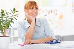 Professionelle schöne junge Frau, die ihren Schreibtisch an ihrem Haus sitzt Stockbilder