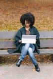 Professionelle schwarze Frau, die mit Laptop draußen im Herbst arbeitet stockfoto