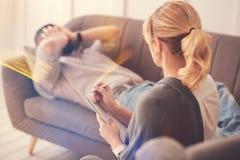Professioneller blonder Therapeut, der ihren Patienten betrachtet Stockbilder