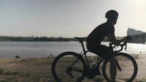 Professioneller d?nner geeigneter Radfahrer auf dem Fahrrad, das auf einer Br?cke ?ber Fluss mit den Autos durch sich bewegen sch stock footage