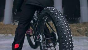Professioneller extremer Sportlerradfahrer, der ein fettes Fahrrad im Freien reitet Radfahrerfahrt im Winter auf Schneeeis Mann t stock footage