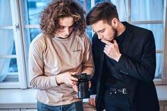 Professioneller gelockter Fotografmann, der Fotos auf Digitalkamera zeigt, um gekleidetem custumer zu entsprechen stockbilder