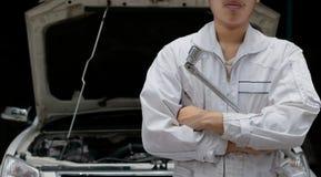 Professioneller junger asiatischer Mechanikermann im einheitlichen haltenen Schlüssel gegen Auto in der offenen Haube an der Repa Lizenzfreie Stockfotos