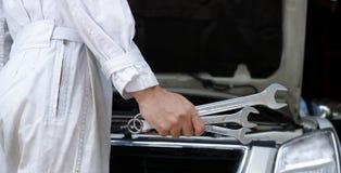 Professioneller junger Mechanikermann in der weißen Uniform, die Schlüssel gegen Auto in der offenen Haube an der Reparaturgarage Stockfotografie