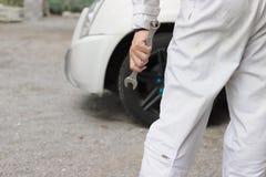 Professioneller junger Mechanikermann im einheitlichen haltenen Schlüssel gegen das Auto bereit, an der Garage zu reparieren Lizenzfreie Stockfotos