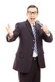 Professioneller männlicher Reporter im schwarzen Anzug, der ein Mikrofon hält Stockfotografie